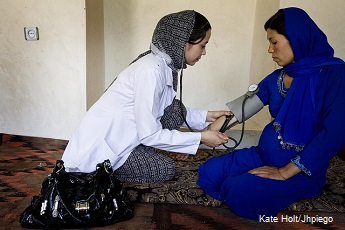 A community midwife takes the blood pressure of a pregnant woman in Jawjzan, Afghanistan