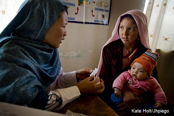 Community midwife in Afghanistan talks with mother (holding baby) about family planning