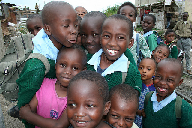 Group of kids smiling outside in a Kenyan slum