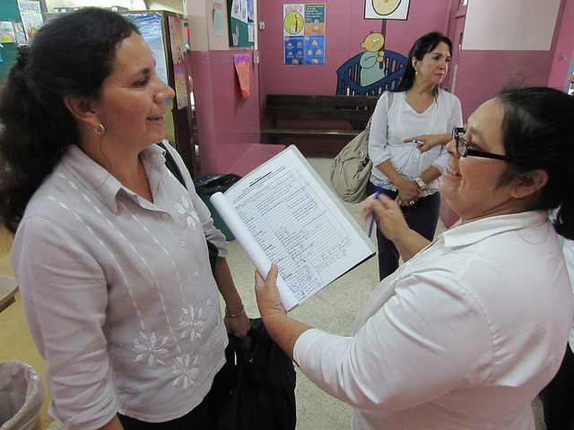 Community Interventions Advisor smiles at hospital staff as they review a chart of data