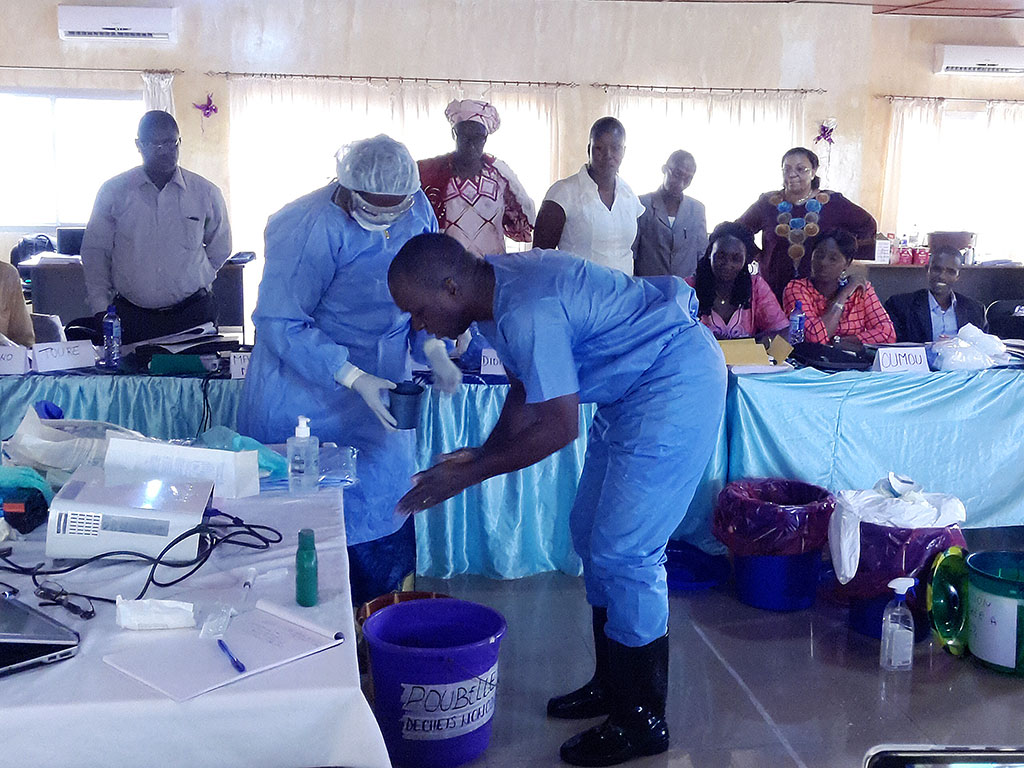 Participants in an infection prevention and control training in Guinea learn key skills.