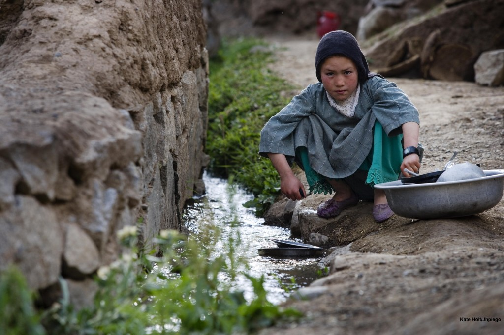 A young girl washes her families pots in a stream outside of the village of Katasank, Bamyan, Afghanistan.