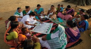 A vaccinator and mothers in India reviewing their community's MVMH tool