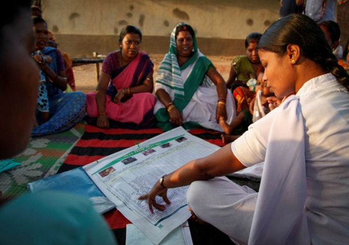 "Community members in a village in eastern India learn about the ""My Village My Home"" tool at a vaccination session."