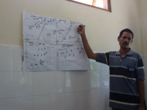 A community leader in Timor-Leste explains his community's map during immunization micro-planning