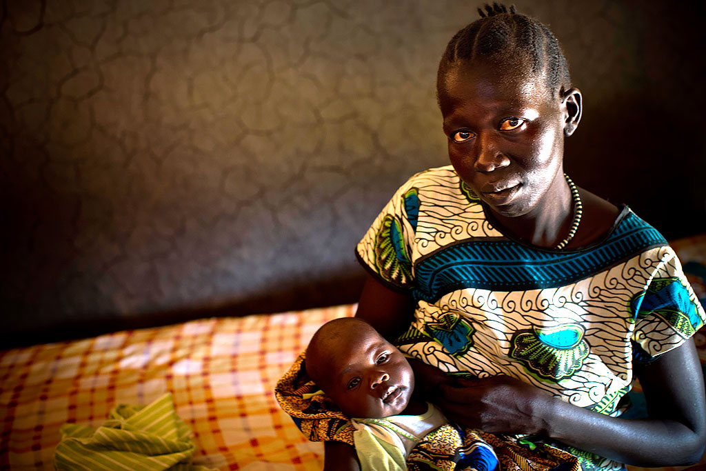 Mother holds her two month old baby, at her home in Lanyi, in Mundri East County South Sudan