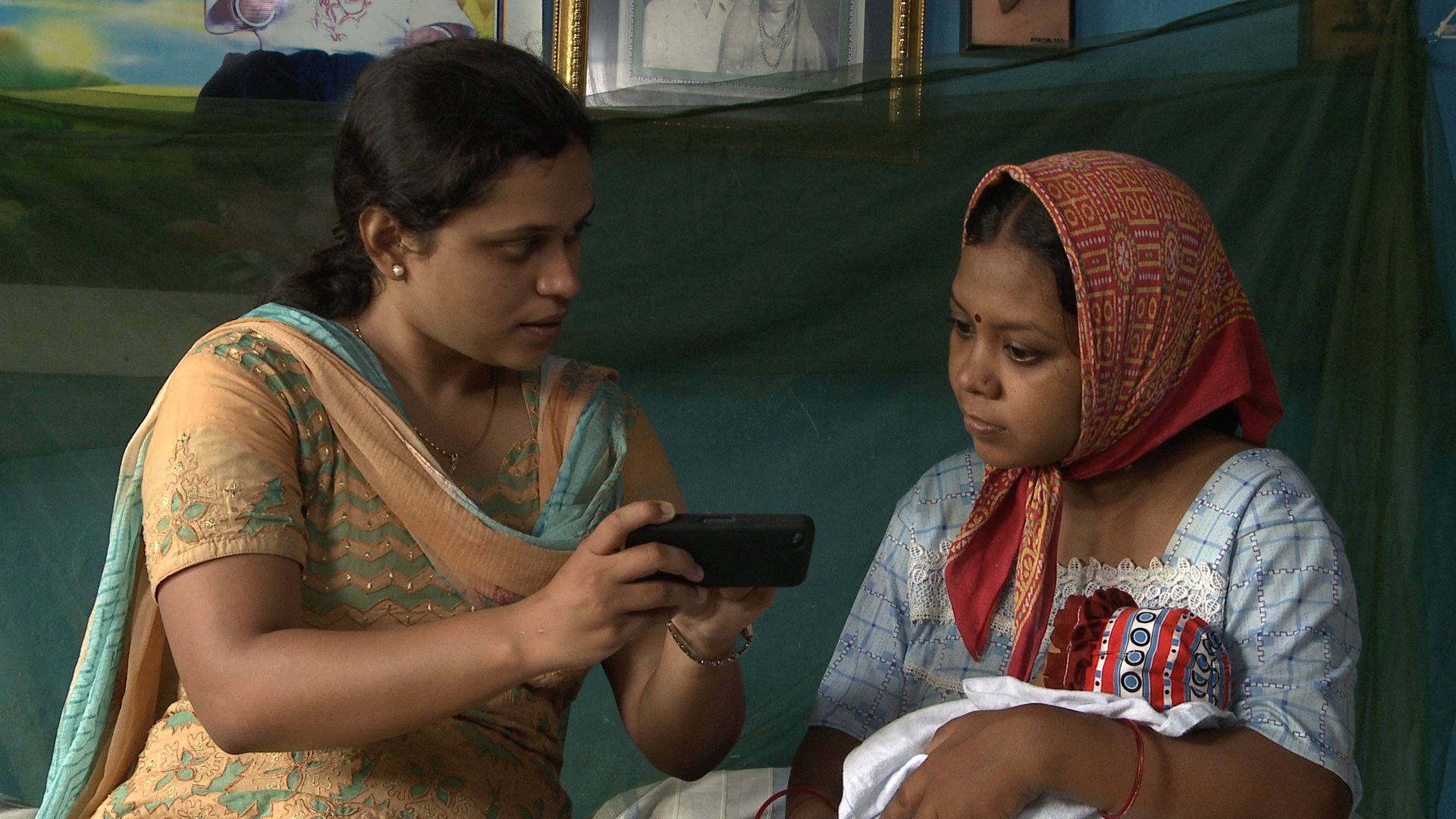 Woman with baby looking at mobile phone