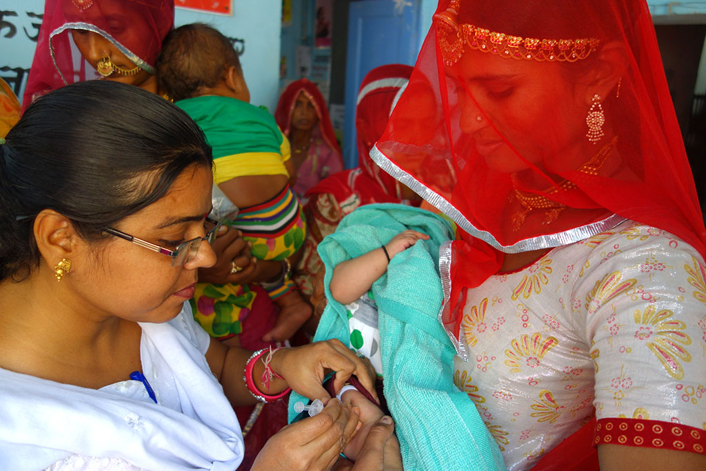A nurse vaccinates children during an immunization camp in Rajasthan, India.