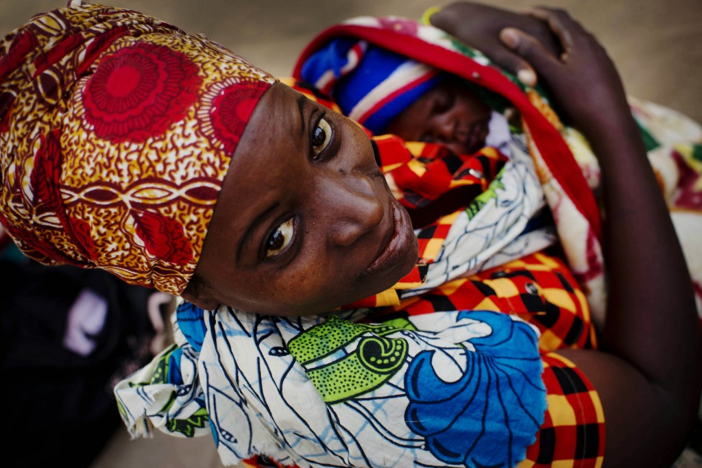 Woman and newborn waiting for a doctor outside a hospital in Nampula, Mozambique.