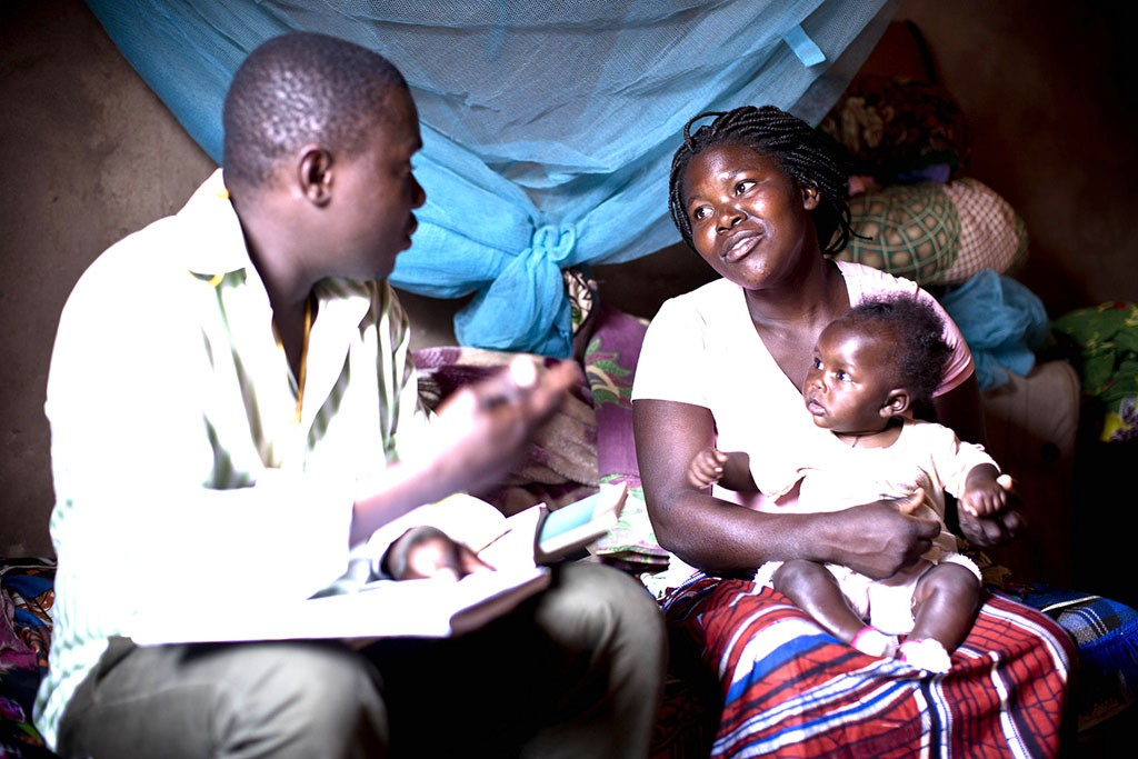 A community health worker visits a mother at home in Mozambique