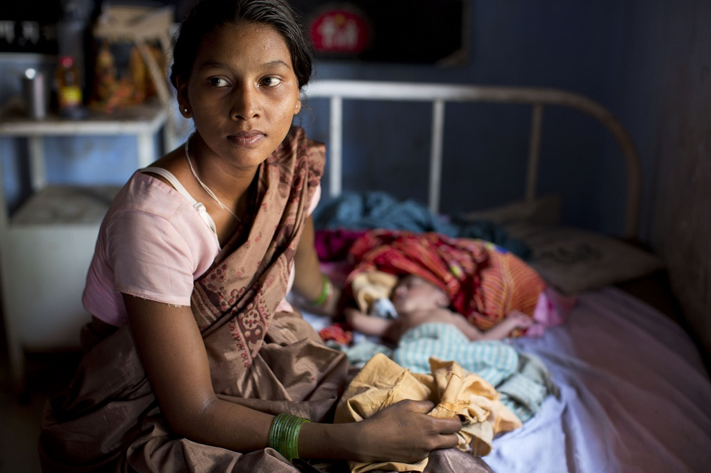 A mother holds her newborn in Kolibera Health Centre near Ranchi, India
