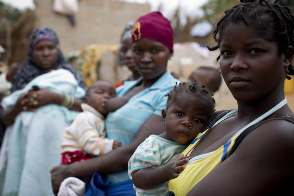 omen wait with their babies outside a health care center in Nampula, Mozambique.