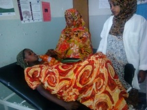 Zerina's mother offers her a drink during labor while Saada observes the patient's status