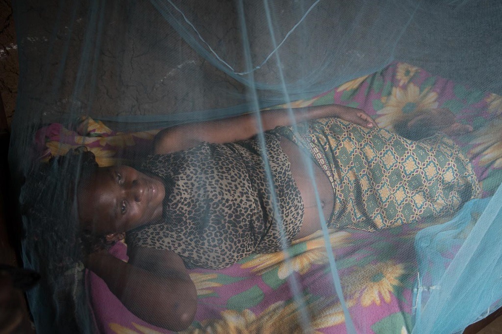 In Kenya, Christine Pepela sleeps under an insecticide-treated bed net provided by a local nurse