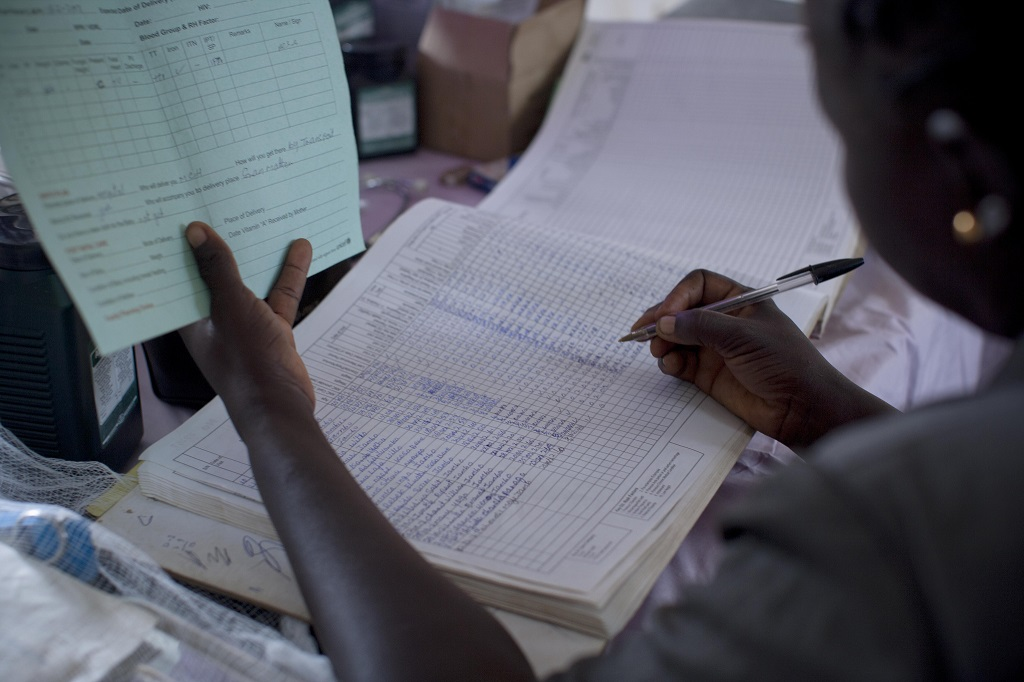 A health care worker fills in a client's reocords at a Primary Health Centre in Mideh in Mundri East County South Sudan