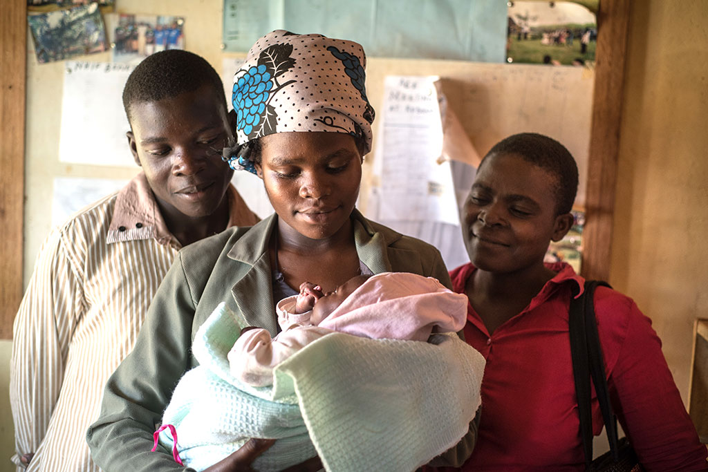 Sarah Naisambu and her husband, Ishmael, hold their daughter, Tabitha, as Joyce Njunukha looks on.