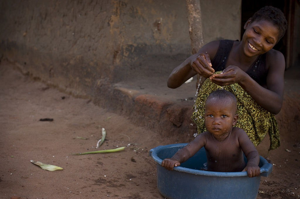 A woman washes her baby in the village of Bokola, Tanzania.