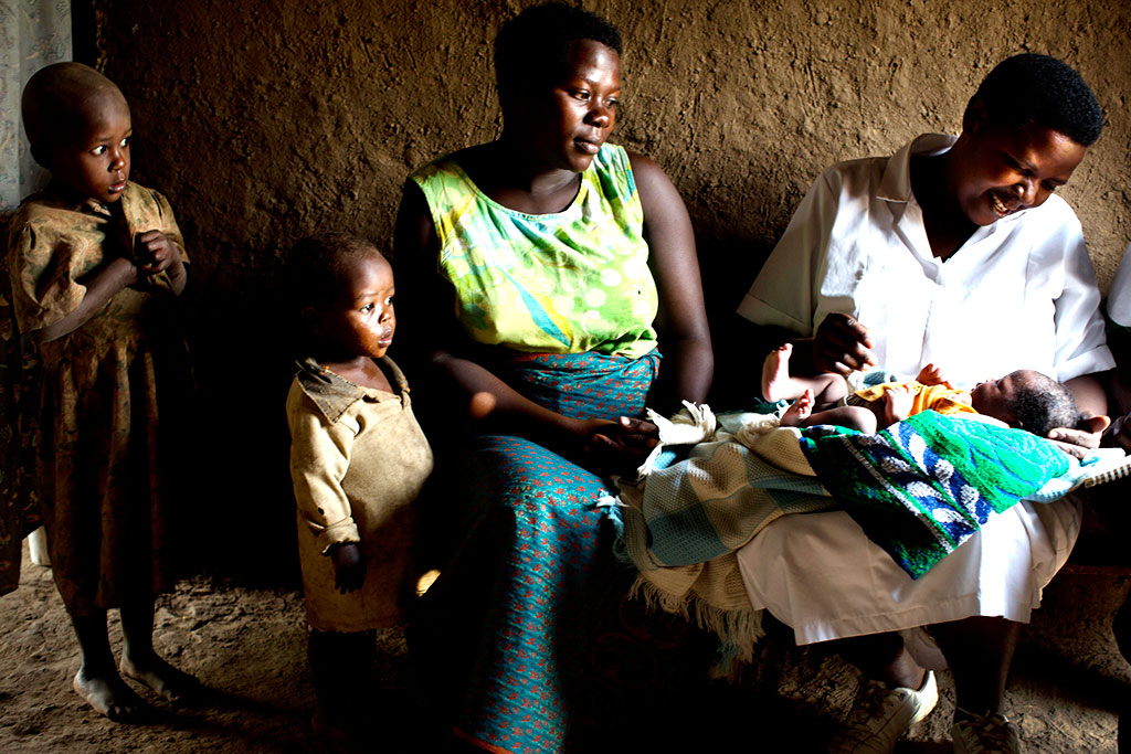 Uganda Mother with family and health worker