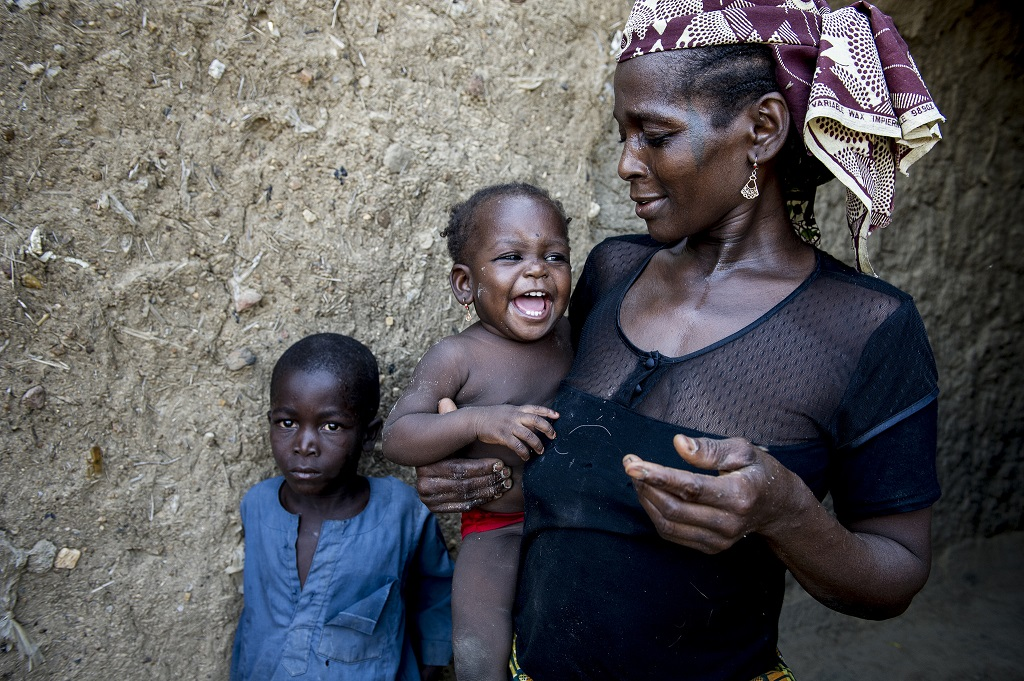 Mother in Nigeria holding her baby and child standing next to them
