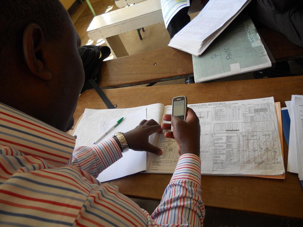 Man entering health facility data into a mobile phone