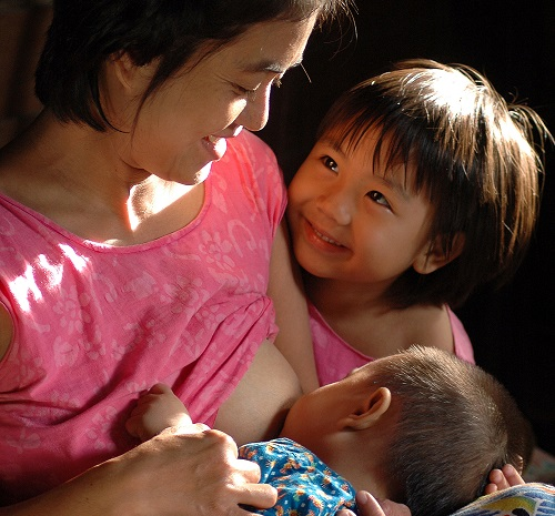 woman breastfeeding a baby with an older child looking on