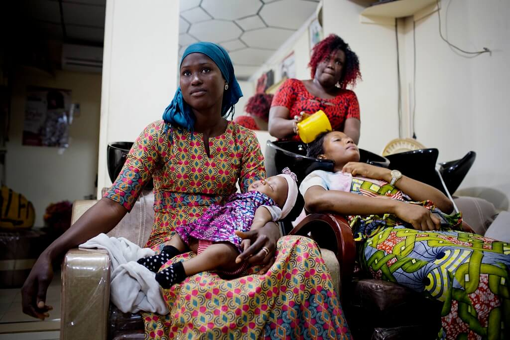 Woman holds her child at a hair salon in Guinea