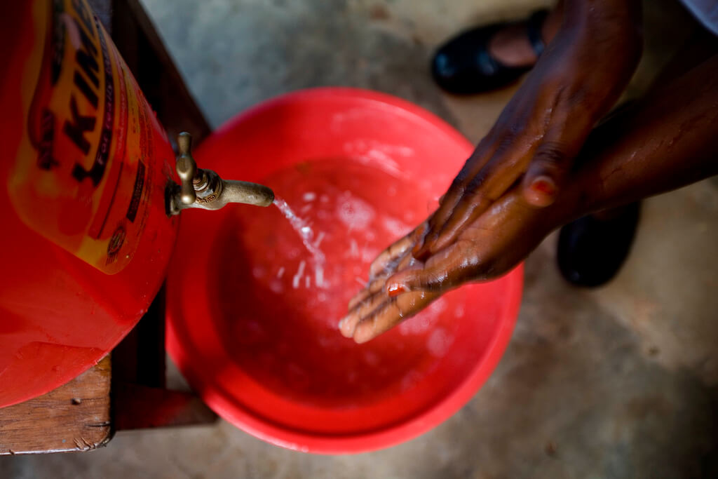 Midwife washing her hands before examining a patient