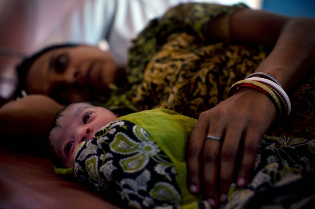Mother and newborn resting at a health facility in India.