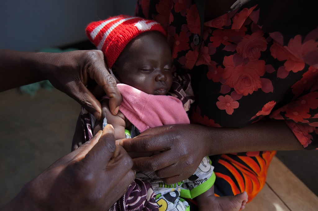 Child receiving a vaccination at a clinic in Malawi