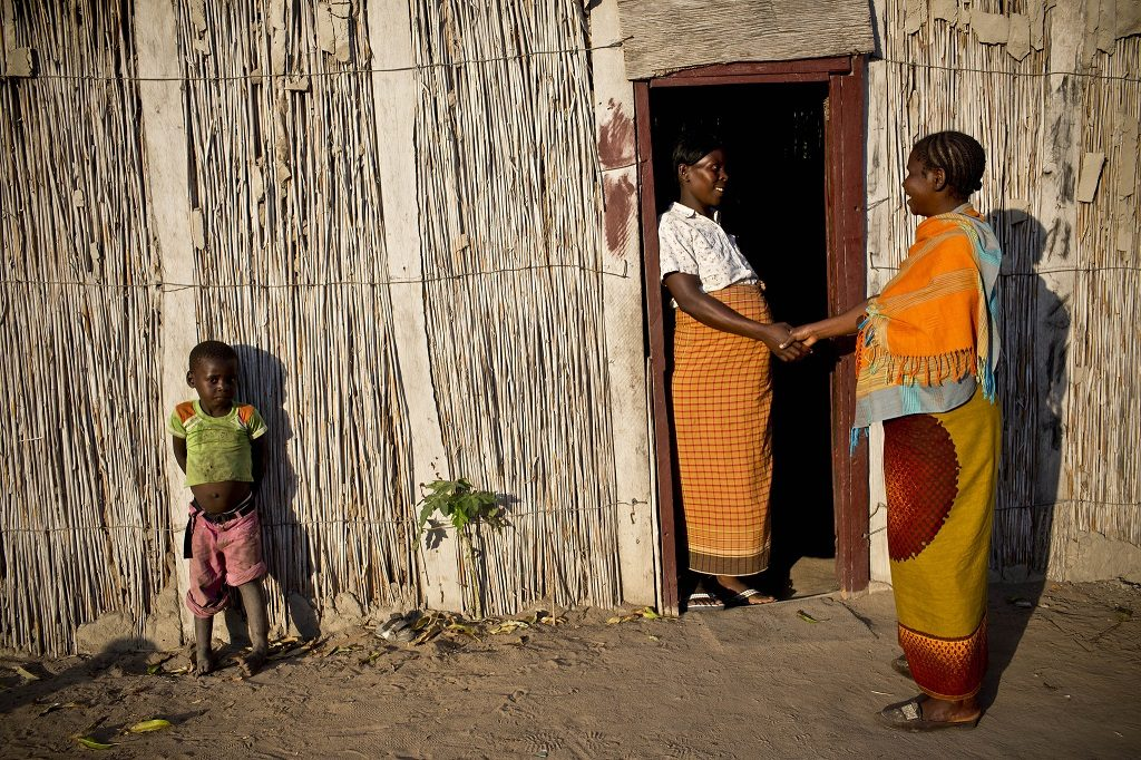 A mother of six children in Mozambique discusses nutrition and family planning with a community health worker at her home.