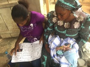 Two young mothers in Nigeria learn how to use chlorhexidine gel with a graphic chart