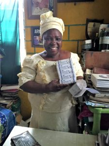 A woman in Nigeria holds boxes of chlorhexidine gel.