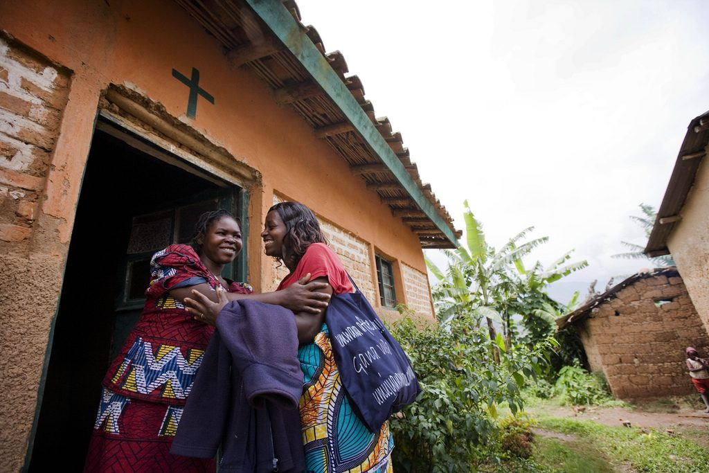 A community health worker greets a pregnant woman outsider her home in Rwanda.