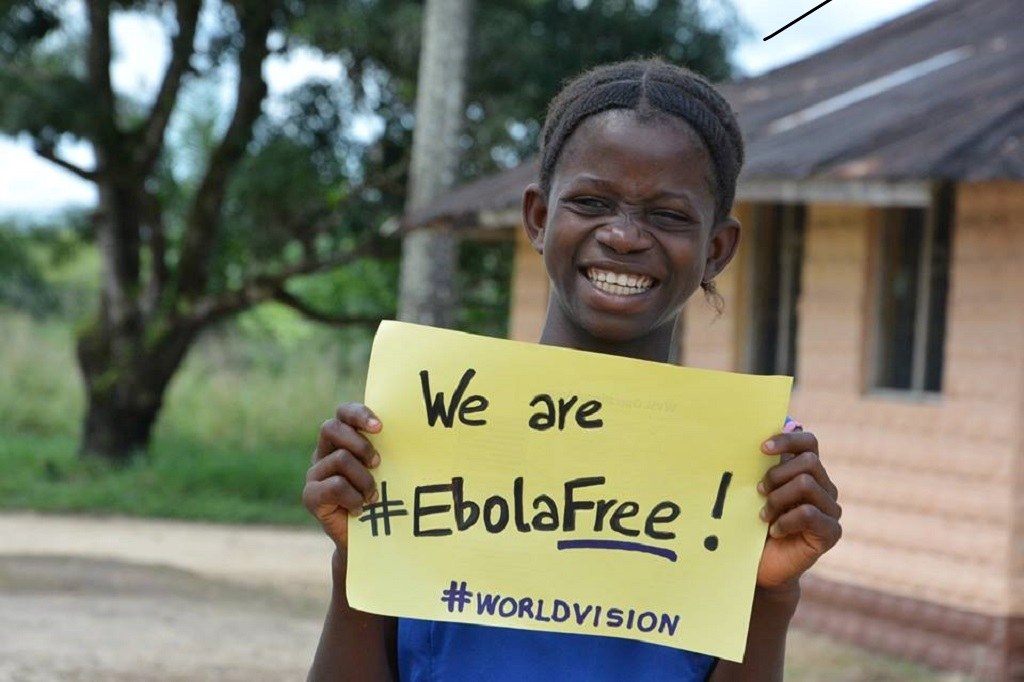 "Girl holding ""we are #EbolaFree!"" sign"
