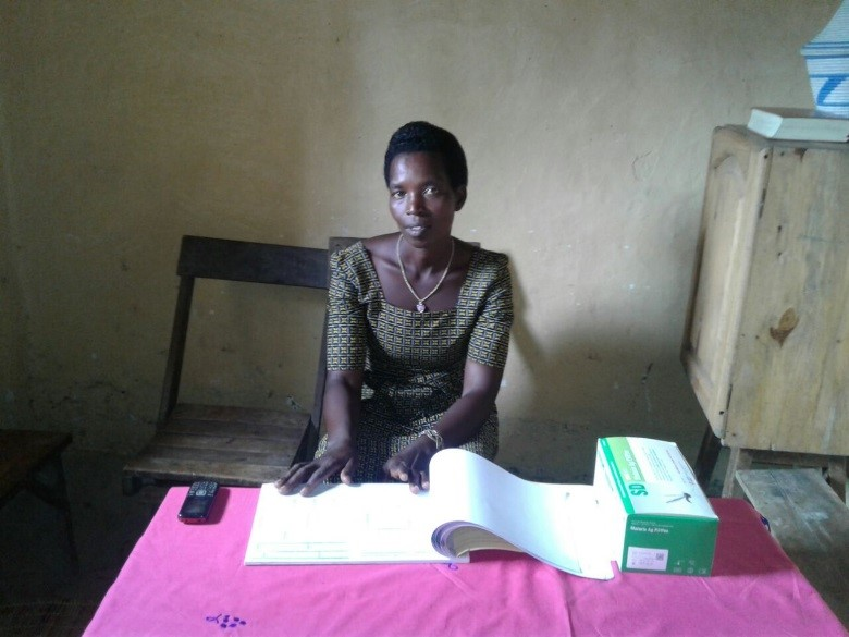 Above: Monique with the iCCM registers and malaria rapid diagnostic tests.