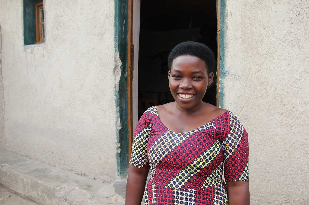 Claudine smiling outside her home in Rwanda