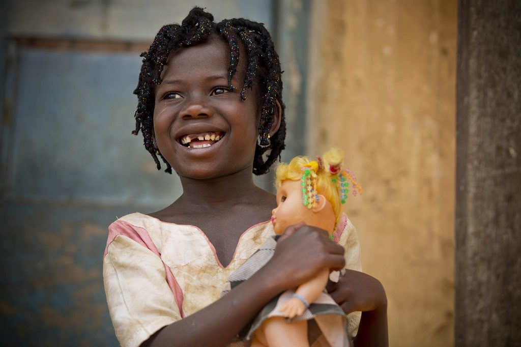 Girl in Ghana holding a doll