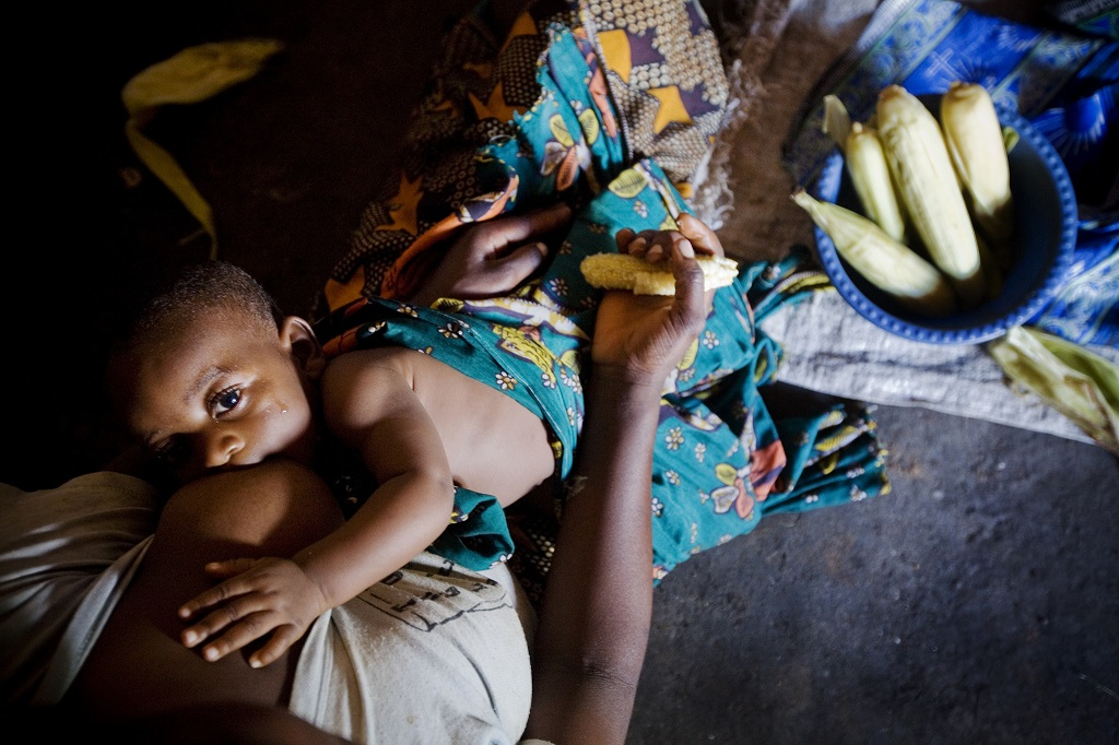 A woman breastfeeds at home in Tanzania.
