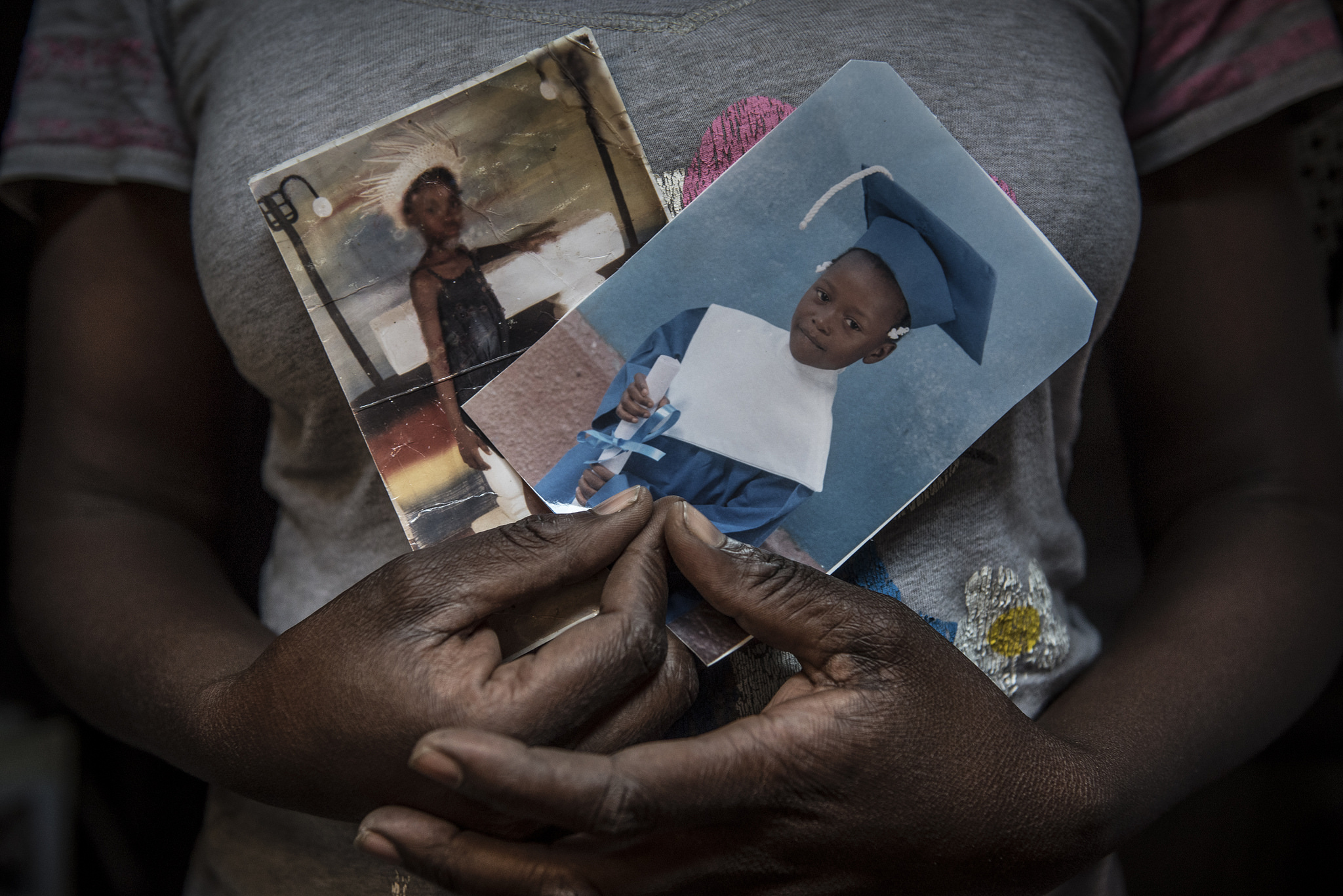 A Haitian mother of three displays pictures of her children, who are in school