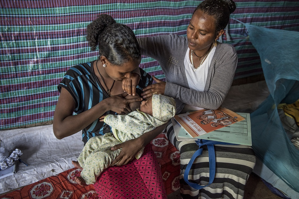 A trained Health Extension Worker in Ethiopia visits the mother of a newborn at home to help her with breastfeeding issues