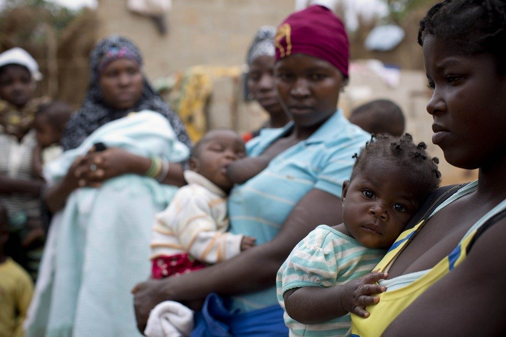 Women wait with their babies outside a maternal health care center in Nampula, Mozambique