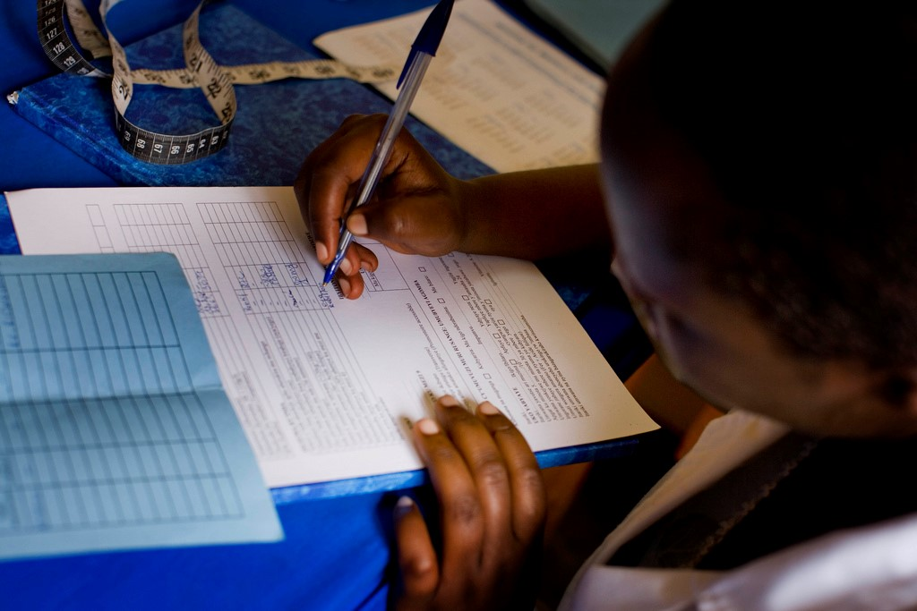 A midwife records medical data for an expectant mother in the maternity unit of Nemba Hospital, Rwanda.