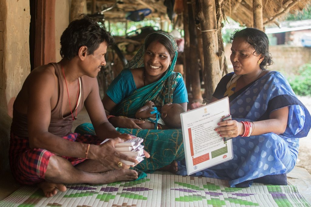 An Indian couple listens carefully to a community health worker, as she talks about the advantages and side effects of modern family planning methods.