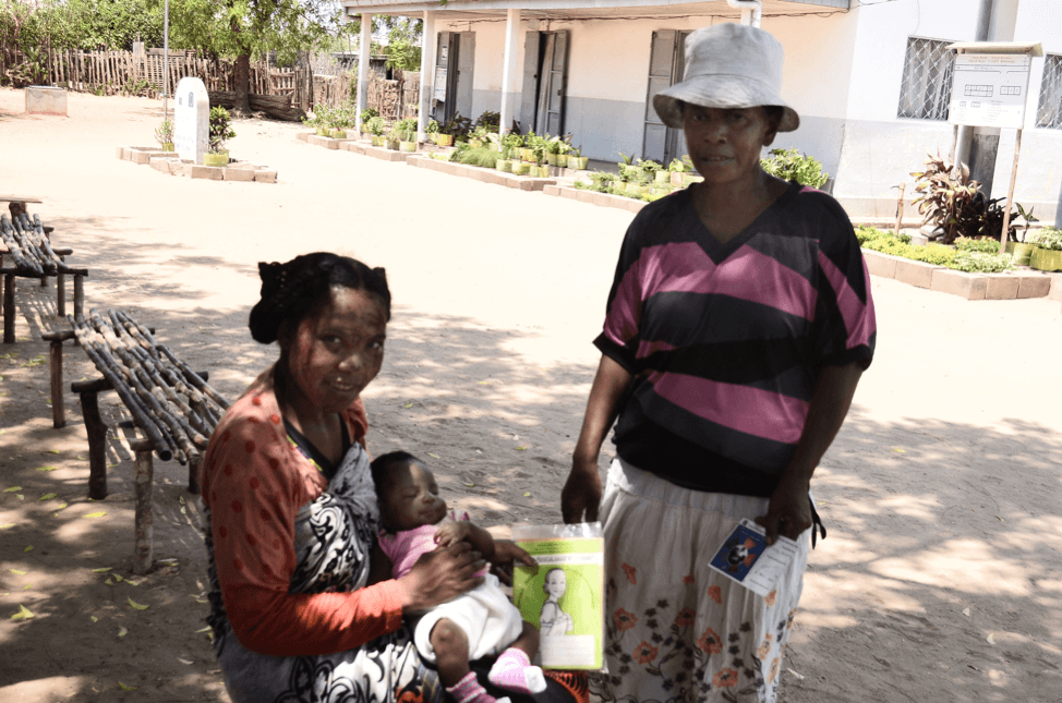 Bemanonga Health Center, Morondava, Madagascar. In her arms, Dorothée holds her daughter and the TMT card that is loaded with helpful information for young mom and first parents. Standing next to her is Roselle, a community health worker empowered by the MCSP TMT initiate.
