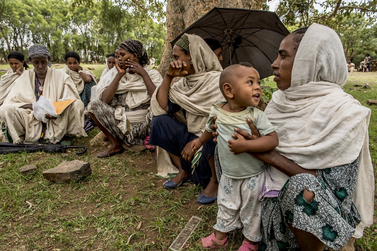Kalkiden Ambew – pictured holding her one-year-old daughter – is pregnant with her second child. She is sitting on the ground with other women.