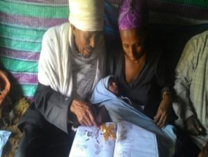 Kes Melakeselam, an Orthodox priest, using a family health guide to educate Abeba Mesele, who recently gave birth to a baby boy.