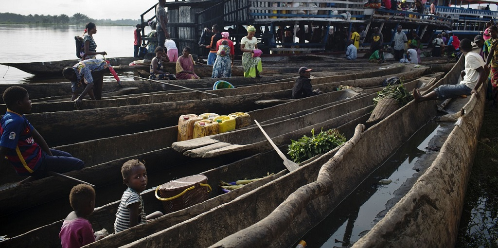 A young girl sits in a pirogue at the main ferry port in Isangi, Tshopo, Democratic Republic of Congo