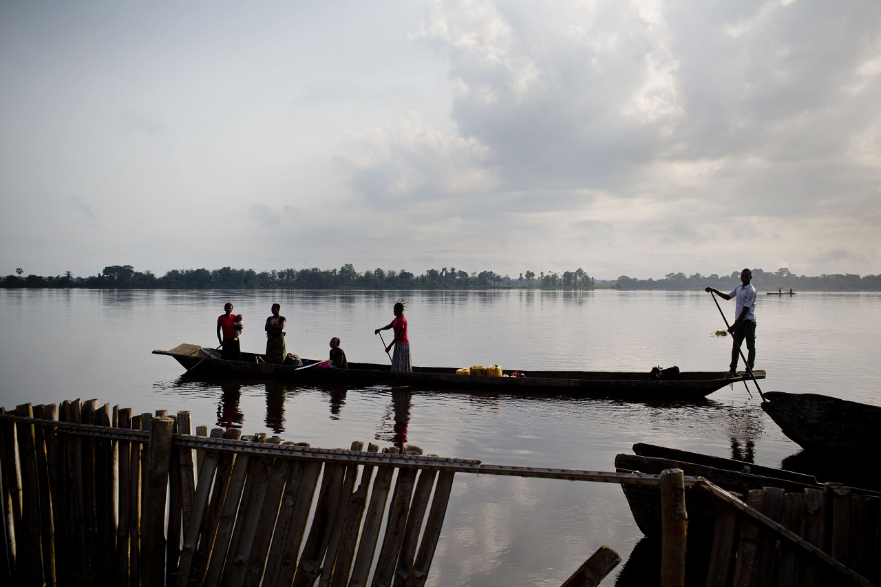 A man paddles a pirogue that is full of people who are needing to go to a health center for treatments near Isangi, Tshopo, Democratic Republic of Congo