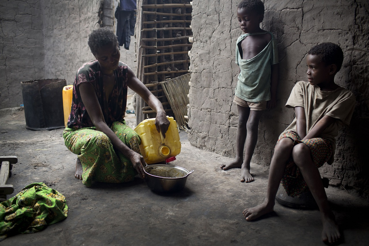 Mother of 10 in DRC pours water into a bowl in their home