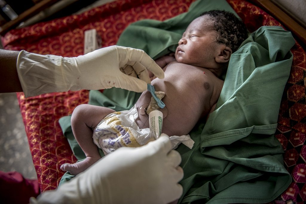 A midwife in Nigeria performing cord care on a newborn.